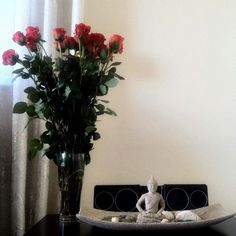 Buddha bedside, red roses.