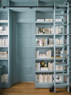 For a book-loving client bound by tight quarters, Washington, D.C.-based designer Lauren Liess doubled her storage space by adding a bank of extra-tall shelves that slides open to reveal a bathroom door.