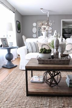 Living room: Grey walls and furnishings, white couch, wooden table decorated with wooden tray and white pots