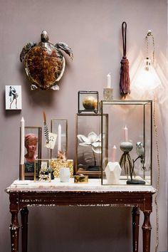 Roze muur met een oude tafel vol glazen stolpen en kistjes | Pink wall with old wooden table and glass boxes | Bron: vtwonen 01 2016 | Fotografie Ernie Enkelaar | Styling Liza Wassenaar & Leonie Mooren