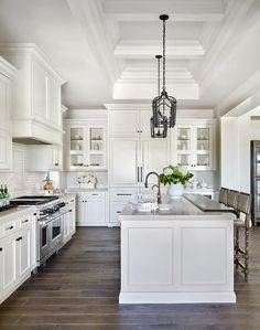 Monochromatic white kitchen boasts Gothic iron lanterns hung from a mini tray ceiling over a white island topped with stained wood countertop fitted with a sink and a gooseneck faucet.