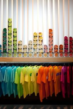 I think this visual merchandising display is very interesting. The way the colors are organized with the shirts hanging below, makes the display very visually appealing. Visual Merchandising Displays, Visual Display, Display Design, Retail Displays, Tshirt Display Ideas Retail, Shop Displays, Window Displays, Booth Displays, Retail Store Design