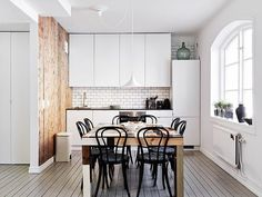 The refrigerator, matching its front to the cabinets so it blends neatly with the rest of the kitchen. Here, instead of open shelving, there are cabinets that take full advantage of the space's height by going all the way to the ceiling.