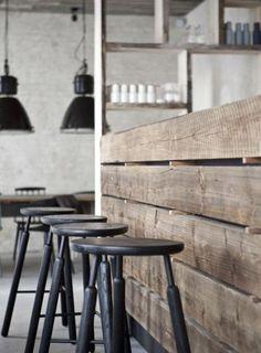comptoir en bois recyclé, bar de cuisine en poutres de bois et tabourets de bar noirs