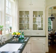 Cream cabinets with black countertops, love the glass doors. Alisberg Parker Architects