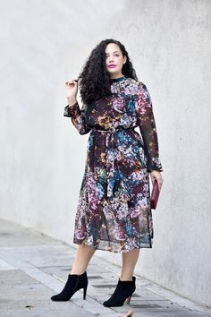 Girl With Curves blogger Tanesha Awasthi wears a long sleeve floral print dress midi dress and booties.