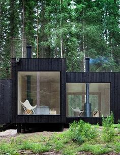 A dark wood cabin in the woods.  I'd love to be sitting in that chair reading a book!