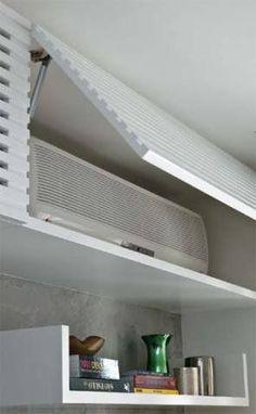 Equipamento disfarçado: no alto da parede, um módulo da estante esconde o ar-condicionado. Ripada, a porta basculante pode ficar fechada mesmo com o aparelho em funcionamento. Projeto de Carla Basiches.