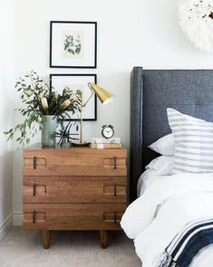 The Dexter Nightstand goes against the grain of its natural walnut make with a contemporary design. Carved details at the corners add dimension to its boxy shape, while vertical black metal hardware add an eclectic touch to its natural wood origins. #Contemporaryfurniturebedroomhomedecor