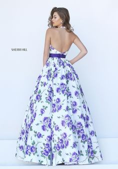 Allover floral print on a white background lends a whimsical touch to this A-line Sherri Hill 50472 prom dress. This style shows off your shoulders with its halter neckline which plunges to the waist in a low V with straps circling the back of the neck, leaving the back open. The natural waistline is defined by a ruched waistband in a matching solid color. Gathered up top, the skirt falls to the floor in a classic A-line silhouette for a turn on the dance floor.