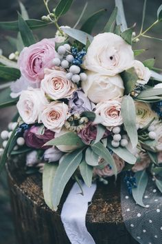 This bouquet represents the perfect winter palette -- soft, dusty green, creamy white, pale lavender, even some sprinkles of faded blue and pink. Wrapped together with satin and polka dot ribbons, this bouquet is pure winter-wonderland perfection.