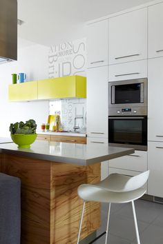 <3 white & grey memories blog.  Small simple kitchen.  Upper cabinets in accent colour, warm wood & white gloss - nice combo.