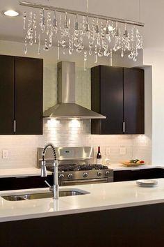 Modern kitchen boasts espresso flat front cabinets paired with white quartz countertops and a white glass mini subway tile backsplash.