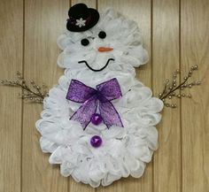 Deco mesh snowman wreath with battery operated lights- purple ribbon.  Perfect decoration to live on all winter long. #decomesh #wreath #snowman #winter #Christmas #gift #homedeco
