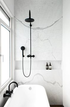 White Statuarietto marble bathroom wall + black shower.