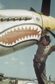 An airman of the 361st Fighter Group with a shark mouth P-51 Mustang.