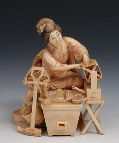 A Japanese ivory okimono Meiji period signed, carved as a woman at a workstation spinning fabric, 10.5cm high