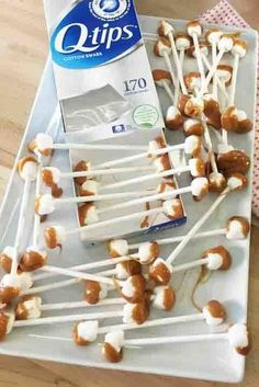 Waxy Q-tips: Place mini marshmallows on both ends of a lollipop stick and dip into warm caramel for a super-sweet bite. For extra effect, empty a box of Q-Tips to place on the platter. Click through for more fun Halloween snacks you and your family will love!