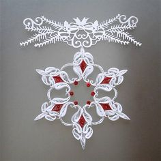 White and red snowflake made of paper strips 3 mm wide. The snowflake ornament is handmade, using quilling techniques (rolling the paper strips and making different shapes and objects). The red diamond-shaped strips have a metallic red edge that gives extra charm and beautifully reflect