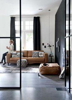 meubles de salon en cuir marron clair, sol gris tapis gris rideaux noirs