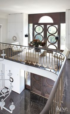 A peek to the foyer from the grand staircase. The custom bronze balustrade and mahogany handrail were custom by interior designer Neal Beckstedt.