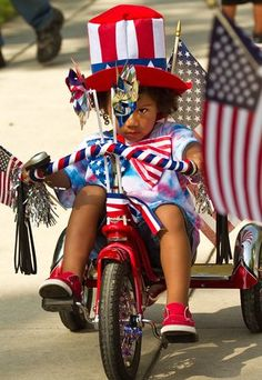 Brilynn Cole, 3, joins the parade of bikes, wagons and scooters decorated for the annual Riverside Citizens Association Fourth of July Pancake Breakfast and Children's Parade in Central Riverside Park in Wichita. (July 4, 2012)
