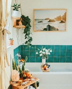 Boho bathroom decor with teal tile around tub