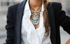 Note the bold necklace worn with a basic, black blazer and white, ruffled blouse.