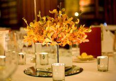 Silver mirror vase with orange orchids