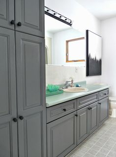 Charocoal painted bathroom cabinets (Rustoleum Cabinet Transformations) with almond sink/toilet, mint green laminate countertop, modern art
