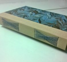 love the criss cross long stitch on this handmade journal with marbled covers