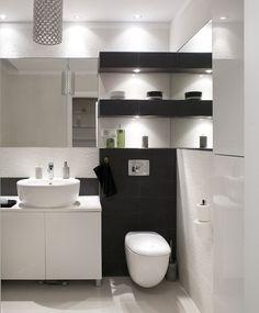 Aranżacja łazienki jest elegancka i stonowana. Mała łazienka, czarno-biała, nie jest zimna, blasku dodaje je dobrze zaprojektowane oświetlenie. Efektownie wygląda też ściana w małej łazience: chropowaty gres, który tworzy doskonałe tło dla nowoczesnego wyposażenia łazienki.