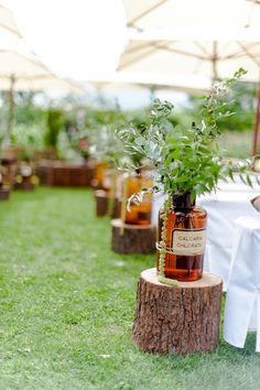 Mittelgang-Dekoration für die Außentrauung mit Holzstämmen und Apotheker-Flaschen sowie Strohballen als Sitzgelegenheit für die Gäste bei www.weddingstyle.de | Foto: von [blickfang] Event Design