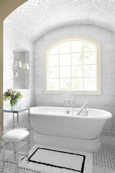A high arch of marble tiles seems to soar above this bathtub and mimics the arch of the window below. Note the size variations of the tile on the wall and ceiling, all different variations of Bianco Carrara marble.