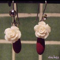 Pendientes colección Rose en color granate. Cada pendiente tiene un gancho con un cristal de Swarovski a juego. Uno de los detalles originales de los pendientes es el abalorio que cuelga tras la rosa en forma de lágrima.
