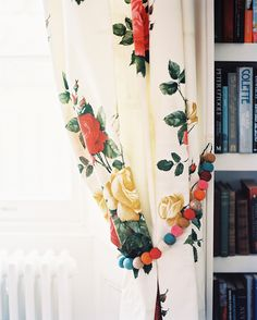 Traditional Details: Floral curtains with beaded tie-backs beside a white bookcase.