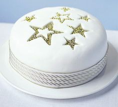 Cut star shapes out of just the fondant layer, ease them out and fill with silver balls. Easy and effective!