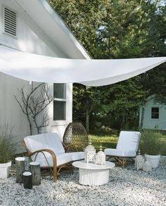 shade sail on a white gravel patio at a summer cottage by the style files, via Flickr