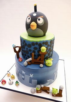 An angry birds Cake cake iced in buttercream, top tier has a fondant wrap. top black bomb bird, made out of krispies and fondant - Ben would love this! Festa Angry Birds, Angry Birds Cake, Pretty Cakes, Beautiful Cakes, Amazing Cakes, Fondant Cakes, Cupcake Cakes, Cookie Cakes, Cookies