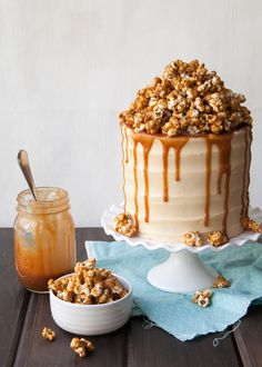 Velvety, brown butter cake is filled and frosted with fluffy peanut butter frosting. To top it all off, add a mountain of caramel popcorn and drippy caramel sauce! Covered in drippy caramel and peanut popcorn, this cake reminds me of going to the circus, summer baseball games, and getting
