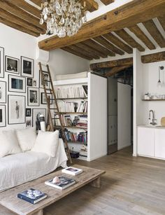 Studio apartment: loft bed, bookshelves, gallery wall, wooden ladder, exposed timber ceiling beams, full-length mirror, chandelier, wooden floorboards, low rectangular wooden coffee table, sofa covered in white sheet, white scatter cushions