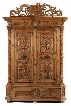 Höhe: ca. 243 cm. Breite: 175 cm. Tiefe: 72 cm. Monogrammiert und datiert 1792. 18. Jahrhundert. Nadelholz, geschnitzt. Sockelgeschoss mit zwei Schubfächern,...