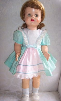 """In 1951 the Ideal Doll Company manufactured a very cute 22"""" doll named Saucy Walker. She became very popular because she walked and was able to stand by herself. This happy faced doll cried and had sleep eyes that were """"flirty"""" (her eyes would move from side to side). Her wigs were braided and could be blonde, tosca, brunette and red. She was marked Ideal/W22 on her neck and back and was dressed in very sweet high quality untagged little girls school type dresses . Saucy could also be 16""""…"""