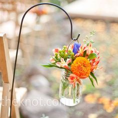 """Rustic Floral Displays    """"Mason jars filled with orange and purple wildflowers hung from shepherd's hooks along the wedding aisle."""""""