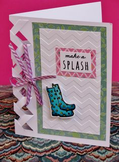 """Sherri Bradley made this card for our Close To My Heart Pretty Gurlz (""""Come as you are; we'll add the Bling!"""") team artwork swap. The adorable rainboots and sentiment are from C1597 Rainy Day My Acrylix stamp set from CTMH. I love how her use of the Chevron Embossing Folder - Z1925 incorporates a sense of playful motion to accent the pretty colors of the Brushed Paper - X7190B . The clever cut out is a fantastic accent along the folded edge all tied up with Thistle Chevron Ribbon."""