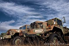 A series of old military trucks rusting in a field.