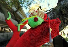 Knitted bugs swarm wooly wrapped trees
