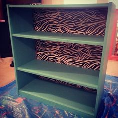 Cheap-o bookshelf...painted in chalk paint and wrapping paper mod podge and distressed on the back...too cute.