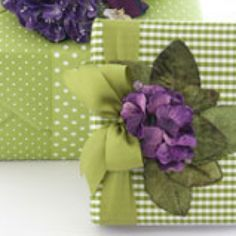 Carolyn Roehm Style...green and purple gift wrap combination.   Green and white gingham check and pin dot print paper with a bunch of violets as a topper and with a complementary ribbon.