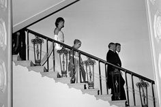 President John F. Kennedy and visiting Tunisian President Habib Bourguiba descend to the Grand Foyer of the White House followed by Moufida Bourguiba and First Lady Jacqueline Kennedy, in 1961. This was the first state dinner held by the Kennedys.
